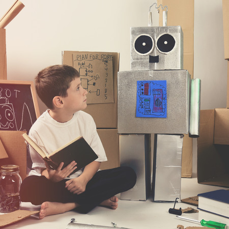 A science student is inventing a metal robot out of cardboard boxes with tools. Use it for an education or imagination concept. Фото со стока
