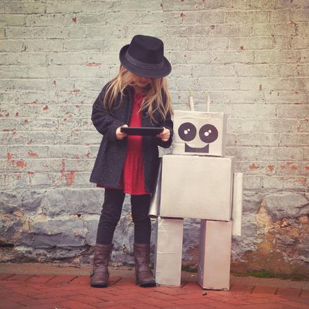 Een klein hipster kind draagt een koel pet houdt een tablet met haar stuk speelgoed robot vriendin de stad in voor een geluk of technologie concept.