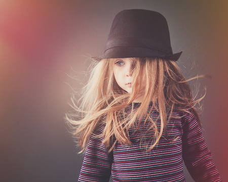 A hipster child with a black hat has her hair blowing and a bright light for a fashion or style concept.