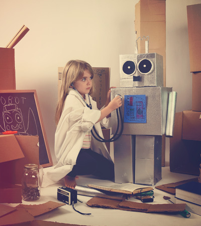 A child science student is inventing a metal robot out of cardboard boxes with tools. The girl is wearing a lab coat. Use it for an education or imagination concept.