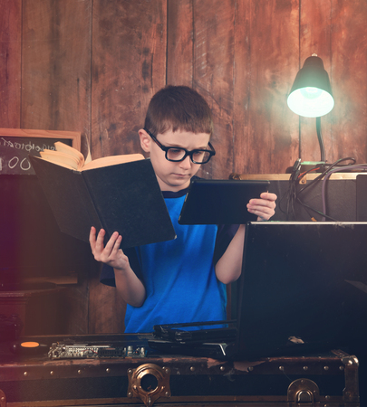 A little boy is reading a science book and holding an internet tablet with computer objects around him for an education or programming concept photo