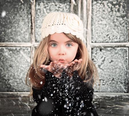 어린 아이는 휴일 크리스마스 또는 계절 개념의 겨울 배경 장면에서 하얀 눈송이 불고있다.