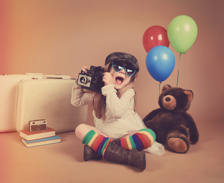 A photo of a vintage child taking a picture with an old camera against with balloons and a teddy bear for a creativity or vision concept.