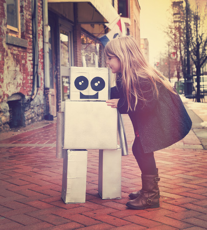 inventor: A little girl is hugging a metal cardboard robot downtown against a brick wall outside for a friendship or inventor concept.