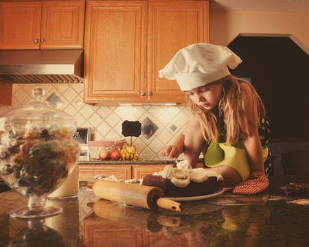A little child is frosting a cake in the kitchen for a bakery, diet or food concept. The girl is wearing a white chef hat.