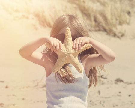A little child is holding a starfish at a beach with sand for a travel vacation or explorer concept. photo