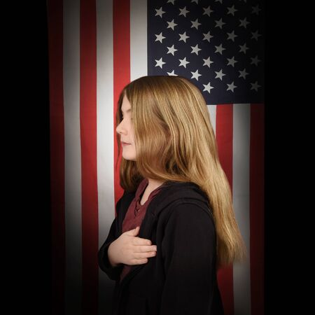 A young american student is saying the pledge of allegiance with her hand on her heart and an american flag in the background for a freedom or patriotic concept.