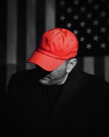 A voter man is wearing a red baseball hat with an american flag in the background for a republican party or maga symbol concept