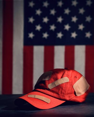 A closeup of a make america great again red baseball hat. The maga hat has an american flag in the background for a republican party symbol Фото со стока