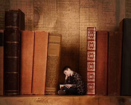 A young child is small and reading a book on a bookshelf with larger books for an adventure fantasy or imagination concept.