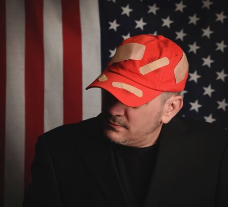 A closeup of a man wearing a red baseball hat with bandage . There is an american flag in the background for a republican party or maga concept.