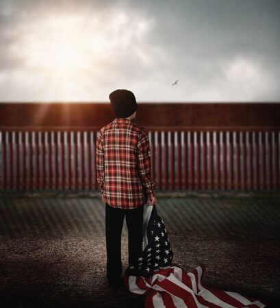 A young immigrant boy is looking at a border wall with an american flag for a freedom or national policy concept. Фото со стока