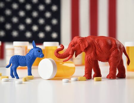 A blue donkey as a democrate and a red elephant as a replublica are against an american flag with prescription pill bottles for a medical cost concept.