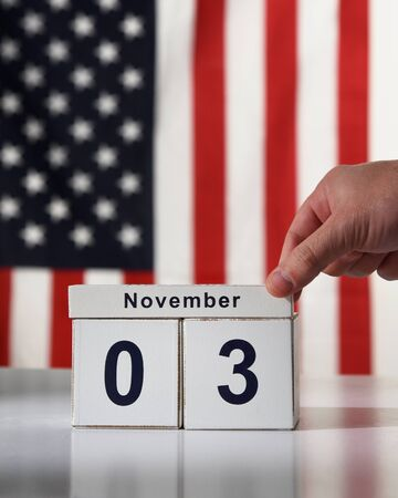 A hand is saving the date of november 3 2020 for the presidential democratic election with an american flag in the background for a voter concept. Фото со стока