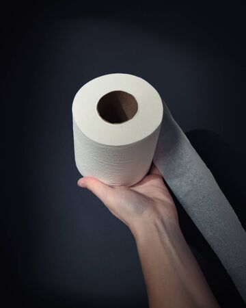 A hand is holding a toilet paper roll with a spotlight on the object for a supply and demand shortage of toilet paper on the corona virus pandemic. Фото со стока