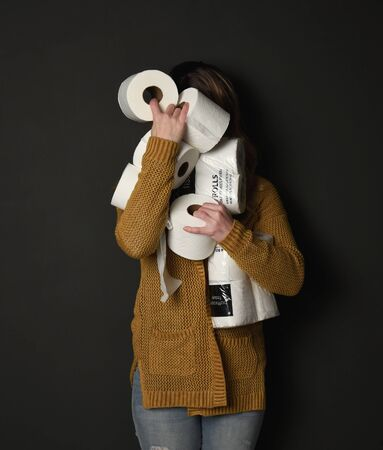 A woman is holding a stock pile of toilet paper supplies for a consumer demand concept regarding the corona virus pandemic.