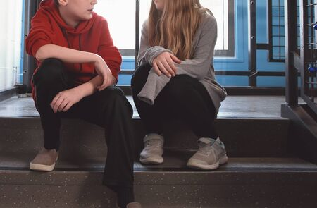 A boy and girl student are sitting in a hallway on stairs talking for a youth communication concept. Фото со стока