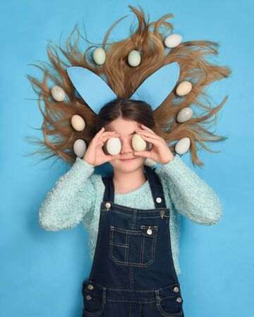 A girl is laying down on a blue background with her hair spread out holding Easter Eggs onto her eyes hiding for a childhood personality concept. Фото со стока