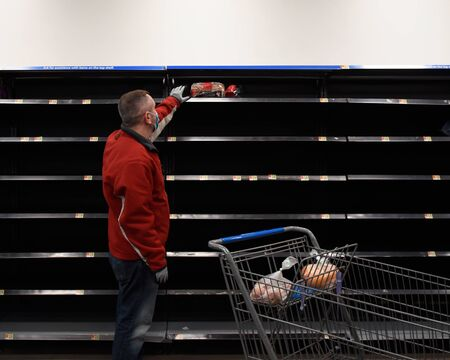 A man is wearing a medical mask at a grocery store reaching for bread with empty shelves for a pandemic emergency concept.