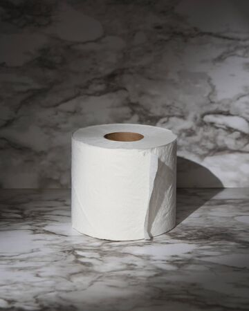 A toilet paper roll with a spotlight on the object for a supply and demand shortage of toilet paper on the corona virus pandemic.