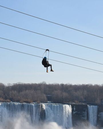 A person is riding a zipline down with the niagara falls waterfall in the background for a vacation tourism activity concept.