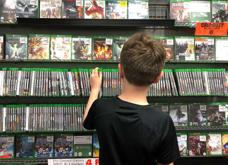 A young boy is buying an xbox one video game at a store for a gamer technology concept. Редакционное