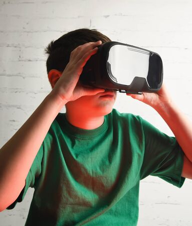 A youth boy is wearing virtual relaity goggles. He is holding the vr device in a room for a tween future technology concept.
