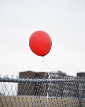 A red balloon is tied to a chain fence outside for a loneliness or solitude concept.