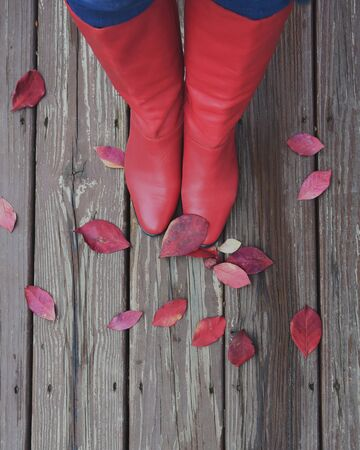 A red pair of women's boots are looking down on fall autumn leaves against a wood floor for a seasonal concept. Фото со стока