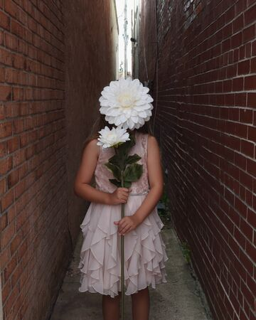 A young girl is holding a large white flower in front of her face in a city ally with brick walls.