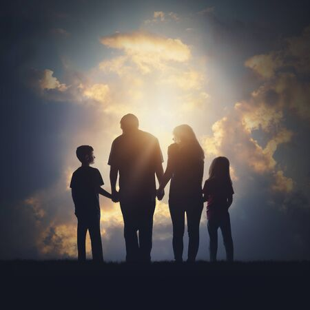A family is standing together outside holding hands with a sky and sunshine for a realtionship bond or faith concept. Фото со стока