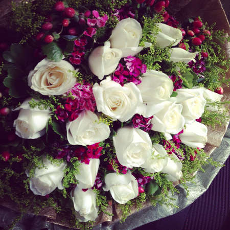 White roses with red berries and lil flora Stock Photo