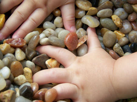 inquiring: Image of a young childs hands reaching into a pile of multicoloured pebbles. Stock Photo