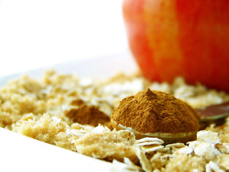 heaping: Image of a heaping spoonful of cinnamon, with brown sugar and oats surrounding and a bright red apple in the background.  Room for text remains in top left hand quarter of the image.  Horizontal orientation.
