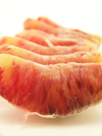 Image of a peeled blood orange, segments lined up in a row.  Vertical orientation.
