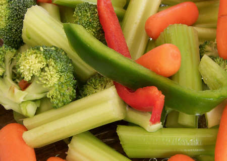 Detailed image of mixed raw vegetables, including celery, broccoli, green and red peppers and  carrots.