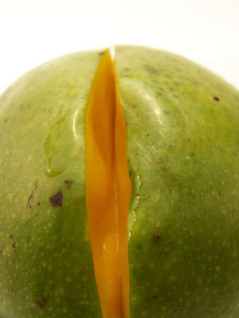 removed: Close up image of a bright green mango with a small slice removed.