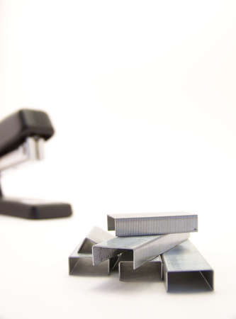office stapler: Image of staple refills in foreground, with black stapler in background.  Vertical orientation.
