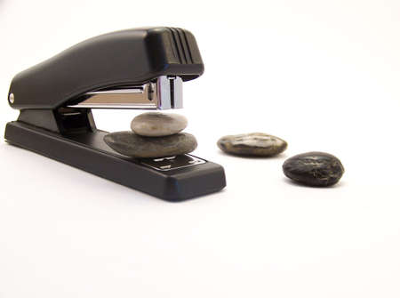 office stapler: Image of a black stapler, about to staple two rocks together, with other rocks nearby.  Horizontal orientation.