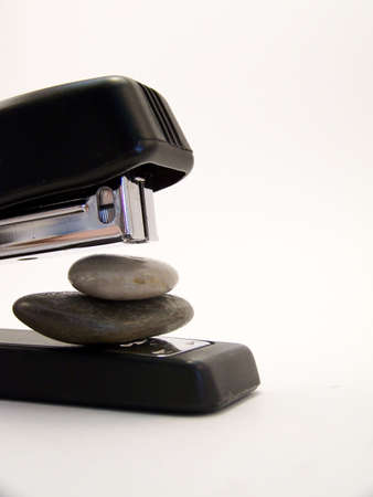 office stapler: Close up image of a black stapler about to staple together two stones.  Vertical orientation.