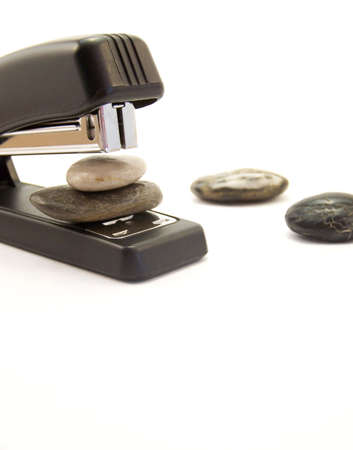 office stapler: Image of a black stapler about to staple two stones together.  Other stones are nearby.  Vertical orientation. Stock Photo