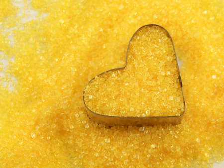cutter: Image of bright yellow sugar and a heart-shaped cookie cutter. Stock Photo