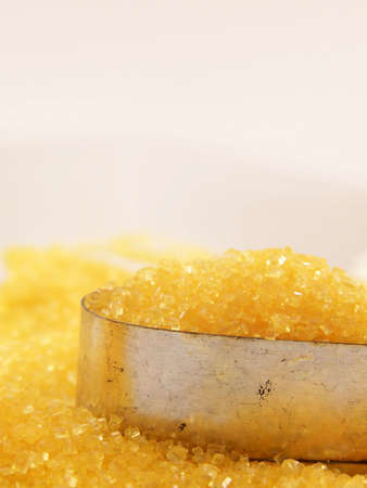 cutter: Image of bright yellow sugar piled into a cookie cutter, with more sugar surrounding.