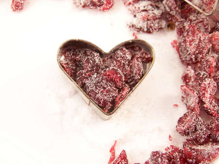 Image of dried cranberries mixed with white granulated sugar, placed in a heart-shaped cookie cutter, with other cranberries surrounding. Stock fotó