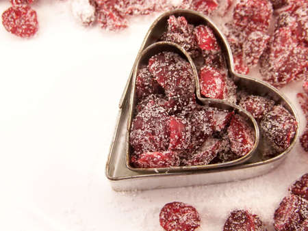 Image of dried cranberries mixed with white granulated sugar, placed within two different sized heart-shaped metal cookie cutters. Stock fotó