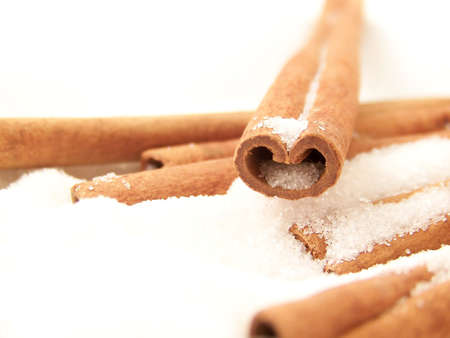 visible: Horizontal image of a heart-shaped cinnamon stick in white granulated sugar, with other sticks visible. Stock Photo