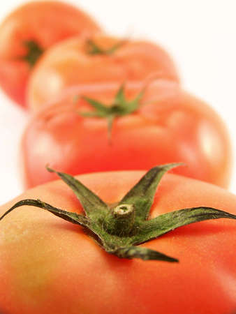 Line of red tomatoes.  Focus is on green stem in foreground. Фото со стока