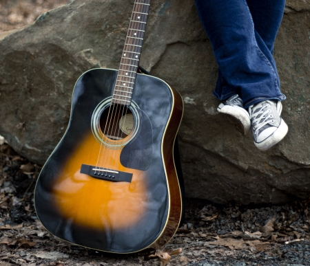 Outdoor scene of acoustic guitar and grey converse