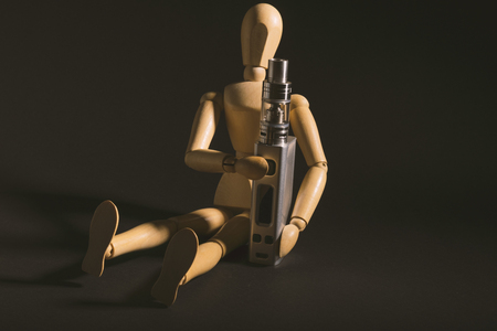 e cig: isolated wooden dummy sitting beside an electronic cigarette or vaping device. isolated on a dark background. Stock Photo