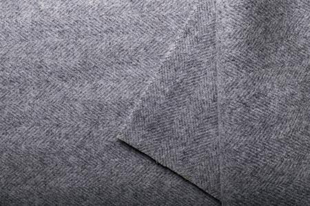 Grey herringbone tweed fabric, herringbone textile background for fashion designers.